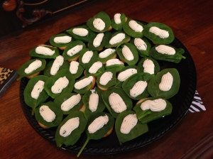 """""""Grubs"""" aka herbed Boursin and cream cheese piped on a spinach leaf and served atop a crostini."""
